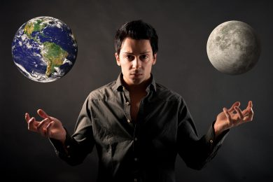 Young man showing hands as a magician with earth and moon.